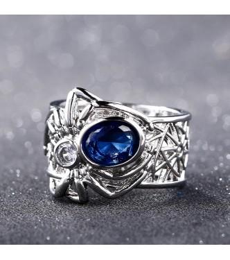 Srebrn prstan s pajkom, ki nosi modri safir